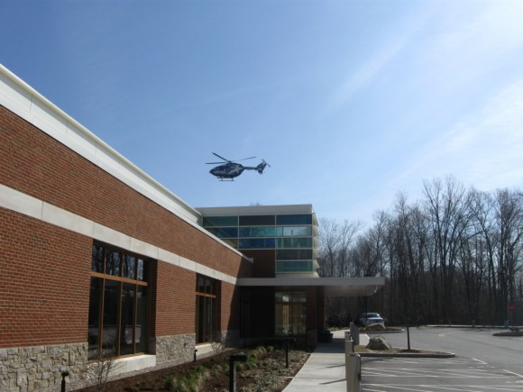 Exterior of Emergency Center with helicopter coming in to land.