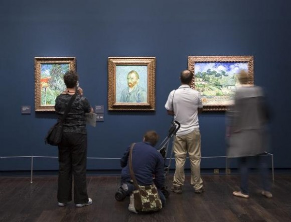 Visitors study the Van Gogh paintings in the new exhibition of the artist's work at the Musee d'Orsay.