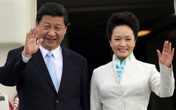 In this file photo, Xi Jinping and his wife Peng Liyuan wave to the crowd.