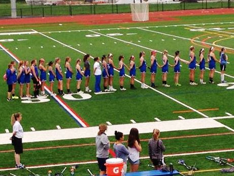 Photo by L. Buckley.  With hands joined in unity, the Old Lyme girls stand to attention during the national Anthem.
