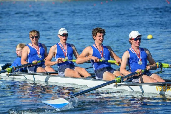 Photo by Brian Corrigan. Rowing away from the award's dock with their silver medals are (from right to left) Liam Corrigan (stroke), Jeremy Newton, Harry Godfrey Fogg, Joshua Swanski and coxswain Tom Crisp.