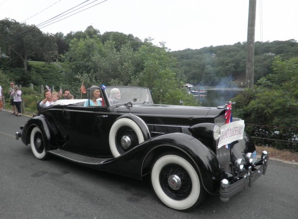 Janis Witkins, Grand Marshal of Lyme's 2015 Independence Day Parade, is driven by George Willauer in his splendid antique automobile.