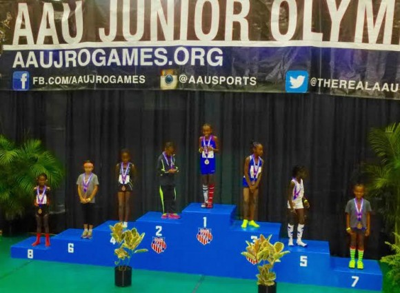 Zoe Eastman-Grossel stands on the medal- winners podium after placing sixth in the Junior Olympics long jump.