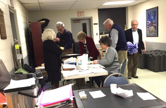 Poll workers tally totals at the Cross Lane FireHouse after voting closed in Tuesday's presidential primary election.